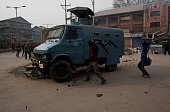 Supporters of Jammu and Kashmir Liberation Front throw chairs at an Indian paramilitary vehicle during a demonstration on December 24 2014 in...