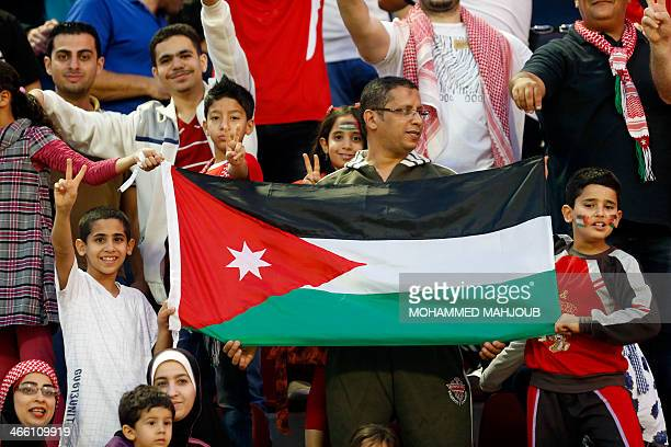 Supporters of Jordanian national football team flash the sign of victory and hold a national flag to cheer their team during the 2015 Asian Cup...