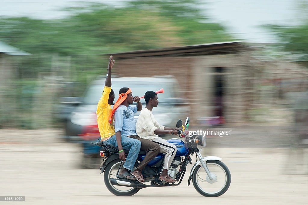 Supporters of Kenyan Prime Minister Raila Odinga's ODM party ride on a motorbike ahead of a CORD Coalition rally in Garsen town, Tana River region, on February 8, 2013 part of campaigning for the upcoming presidential, parliamentary and local elections on March 4. The risk of political violence in Kenya is 'perilously high' ahead of next month's election, the first since bloody post-poll violence five years ago, Human Rights Watch (HRW) warned. AFP PHOTO/Will Boase