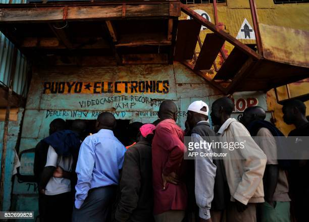 TOPSHOT Supporters of Kenya's embattled opposition leader Raila Odinga gather at an electronics repair shop to watch Odinga on television as he gives...