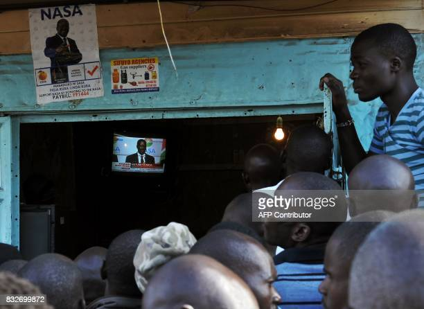 Supporters of Kenya's embattled opposition leader Raila Odinga gather at an electronics repair shop to watch Odinga on television as he gives a press...