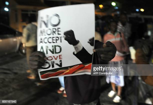 Supporters of Kenya's embattled opposition leader Raila Odinga wave placards and shout slogans as they demonstrate outside The Supreme Court in...
