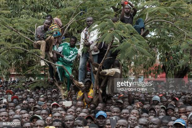 TOPSHOT Supporters of Kenya's opposition National Super Alliance coalition climb a tree to watch the funeral service for the three victims who were...