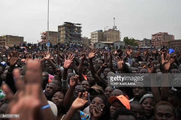 Supporters of Kenya's opposition National Super Alliance presidential flagbearer Raila Odinga cheer as he addresses a political rally on September 3...