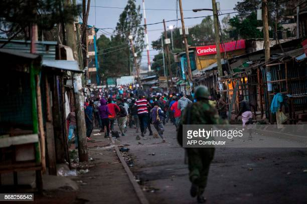 TOPSHOT Supporters of Kenya's opposition National Super Alliance run from police as they demonstrate following the announcement of results of a...