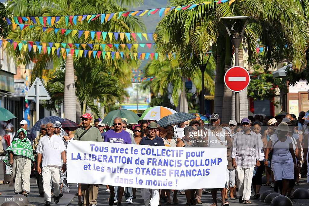 Supporters of kidnapped French engineer Francis Collomp, walks in Le Port, on the French Indian Ocean island of Reunion, on January 20, 2013 during a march demanding his release. The radical Islamist group Ansaru claimed the recent kidnapping in northern Nigeria of Collomp, citing France's push for a military intervention in Mali as a justification. Ansaru, 'announces to the world, especially the French government, that it was responsible for the abduction of engineer Francis Collomp, 63, working for the French company Vergnet,' a statement emailed to journalists said. AFP PHOTO / RICHARD BOUHET