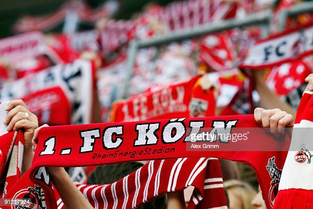 Supporters of Koeln hold up their scarves before the Bundesliga match between 1 FC Koeln and Bayer Leverkusen at the Rhein Energie stadium on...