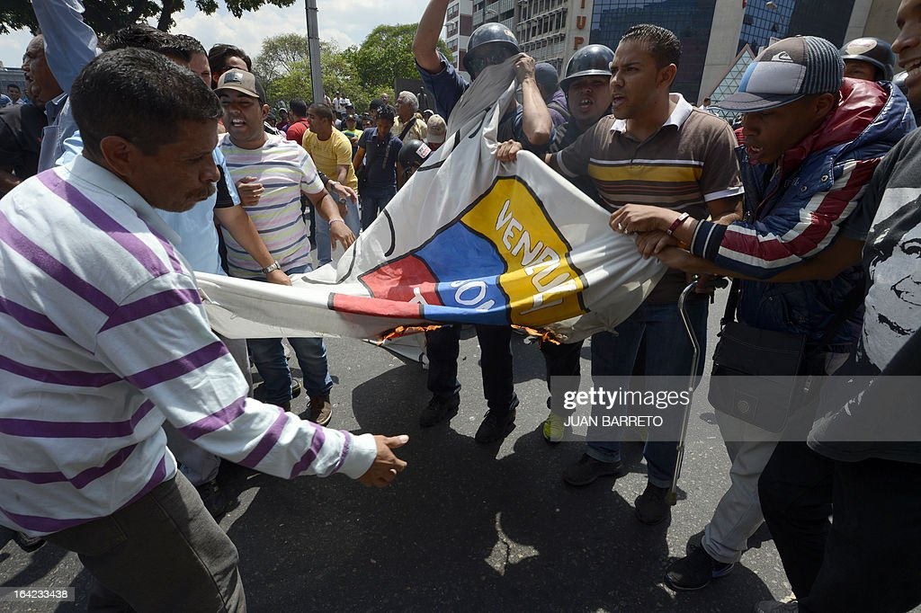 Supporters of late President Hugo Chavez burn a banner of opposition presidential candidate Henrique Capriles in downtown Caracas on March 21, 2013 during a demonstration of opposition students demanding to the National Electoral Council (CNE) transparency during the presidential elections next February 14.