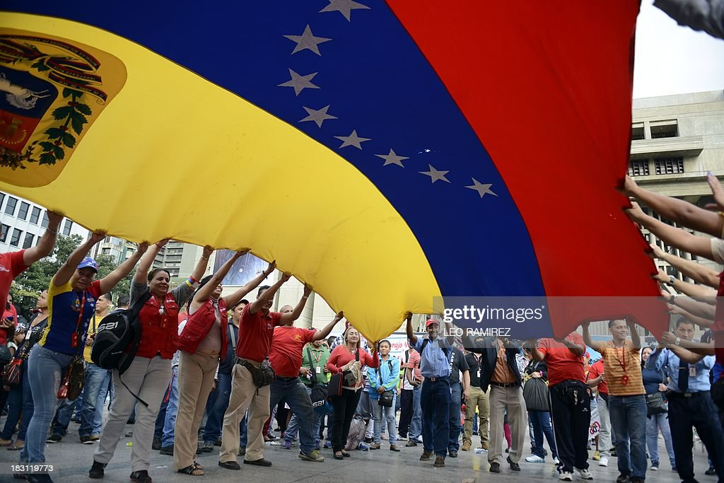 Supporters of late Venezuelan President Hugo Chavez hold a Venezuelan flag during the commemoration of the first anniversary of his last presidential campaign in Caracas on September 4, 2013. AFP PHOTO/Leo RAMIREZ