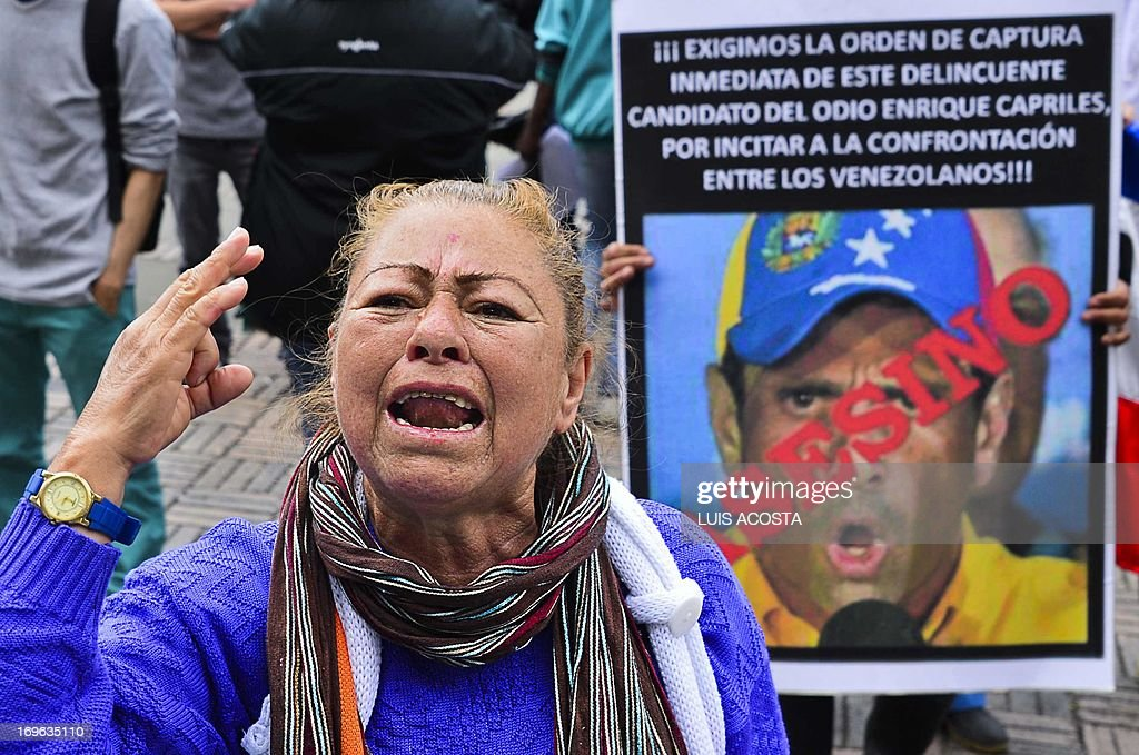 Supporters of late Venezuelan president Hugo Chavez shout slogans against Venezuela's opposition leader Henrique Capriles at Bolivar Square in Bogota on May 29, 2013. AFP PHOTO/ Luis Acosta