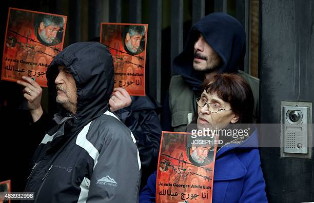 Supporters of Lebanese militant Georges Ibrahim Abdallah hold up placards bearing his portrait and slogans in French and Arabic reading 'I am Georges...