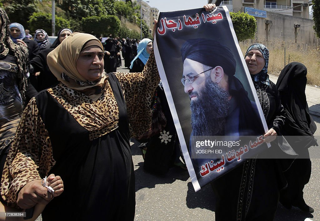 Supporters of Lebanese radical cleric Ahmad al-Assir hold a poster of him as they demonstrate after Friday prayers in the Abra district of the southern Lebanese city of Sidon on July 5, 2013. Assir, a radical Salafi on the run since deadly clashes between his forces and the country's army last month, urged his supporters to turn out to a Friday rally.