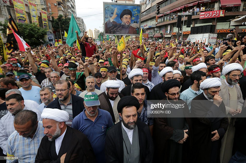 Supporters of Lebanon's Hezbollah group hold a picture of the group's leader Hassan Nasrallah as they march during a rally in southern Beirut to denounce a film mocking Islam on September 17, 2012. Hezbollah chief Hassan Nasrallah, who made a rare public appearance at the rally, has called for a week of protests across the country over the low-budget, US-made film, describing it as the 'worst attack ever on Islam.' AFP PHOTO / JOSEPH EID