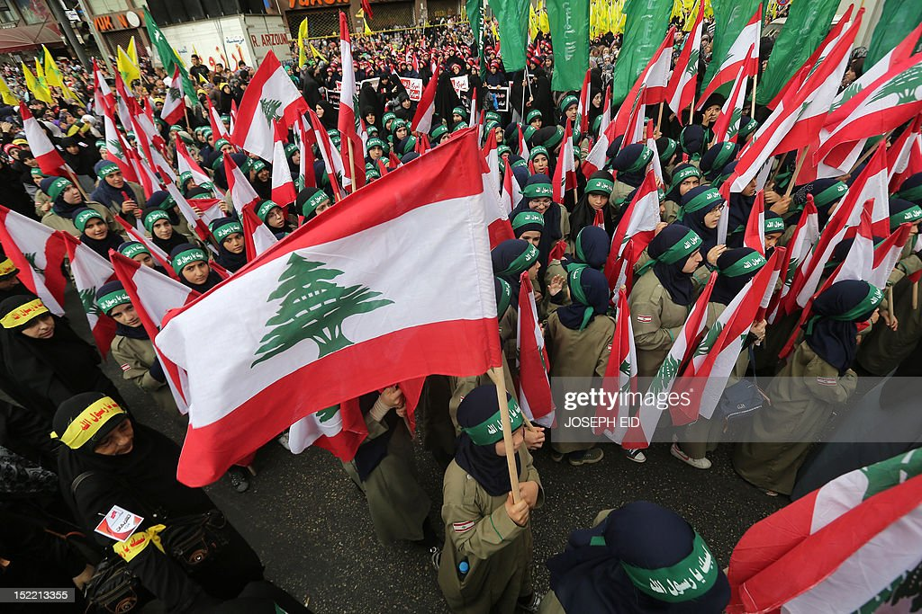 Supporters of Lebanon's Hezbollah group march with Lebanese flags during a rally in southern Beirut to denounce a film mocking Islam on September 17, 2012. Hezbollah chief Hassan Nasrallah, who made a rare public appearance at the rally, has called for a week of protests across the country over the low-budget, US-made film, describing it as the 'worst attack ever on Islam.' AFP PHOTO / JOSEPH EID
