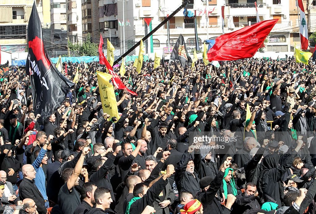 Supporters of Lebanon's militant Shiite Muslim movement Hezbollah shout slogans during a parade as part of the Ashura commemorations that mark the...