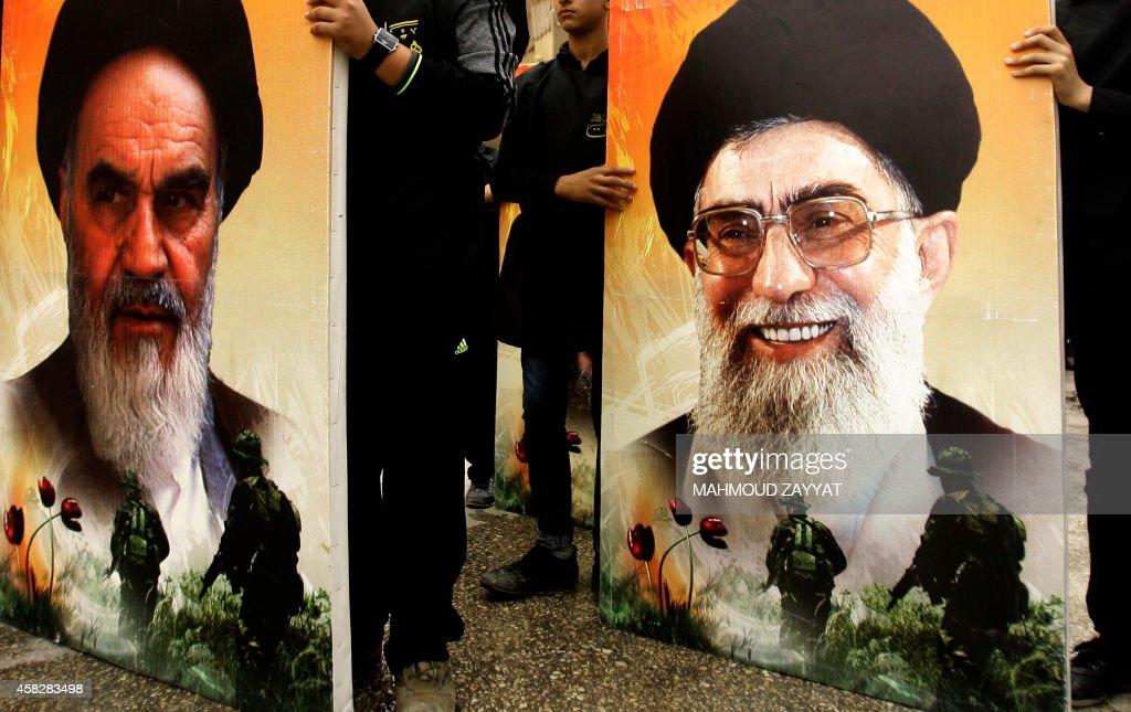 Supporters of Lebanon's militant Shiite Muslim movement Hezbollah carry posters of Iran's late founder of the Islamic Republic Ayatollah Ruhollah...