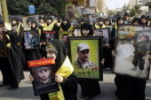 Supporters of Lebanon's militant Shiite Muslim movement Hezbollah show portraits of killed Hezbollah fighters on November 17 2013 in the southern...
