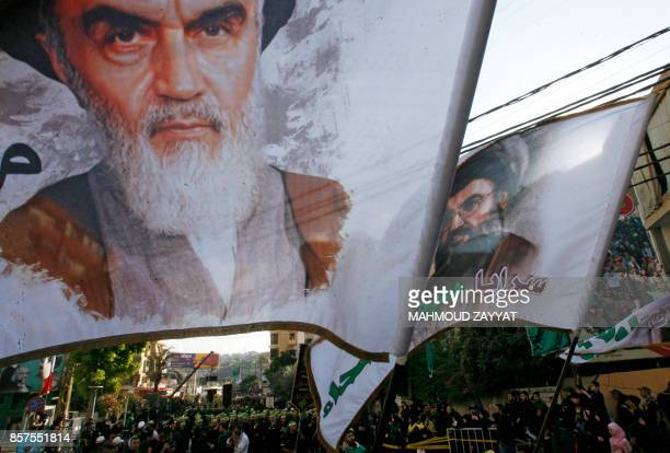 Supporters of Lebanon's Shiite Hezbollah movement wave flags bearing portraits of Iran's late founder of the Islamic Republic Ayatollah Khomeini and...