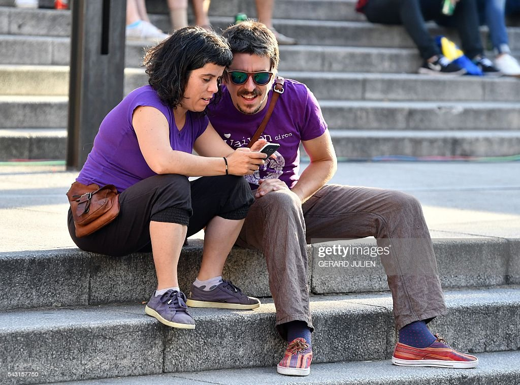 Supporters of left wing party Podemos check the first exit poll on a cell-phone during Spain's general elections in Madrid on June 26, 2016. Spain's ruling conservative Popular Party (PP) took first place in a repeat general election on June 26 but fell well short of a majority while far-left formation Unidos Podemos came second, an exit poll showed. / AFP / GERARD