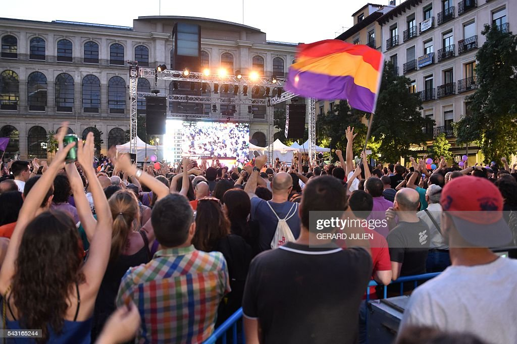 Supporters of left wing party Podemos gesture as they wait for Podemos's leader during Spain's general elections in Madrid on June 26, 2016. Spain's ruling conservative Popular Party (PP) took first place in a repeat general election on June 26 but fell well short of a majority while far-left formation Unidos Podemos came second, an exit poll showed. / AFP / GERARD