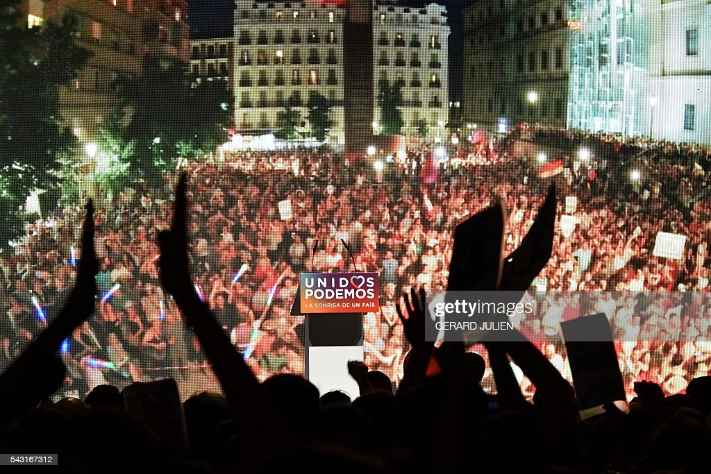 Supporters of left wing party Podemos gesture at Reina Sofia square before the official results during Spain's general elections in Madrid on June 26, 2016. Spain's second elections in six months was due to conclude on June 26 in much the same way as they did in December, with the incumbent conservatives winning tailed by the Socialist party, partial results showed. / AFP / GERARD