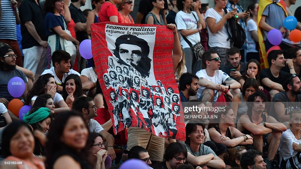 Supporters of left wing party Podemos hold a piece of fabric depicting revolutionary icon Ernesto 'Che' Guevara during Spain's general elections in Madrid on June 26, 2016. Spain's ruling conservative Popular Party (PP) took first place in a repeat general election on June 26 but fell well short of a majority while far-left formation Unidos Podemos came second, an exit poll showed. / AFP / GERARD