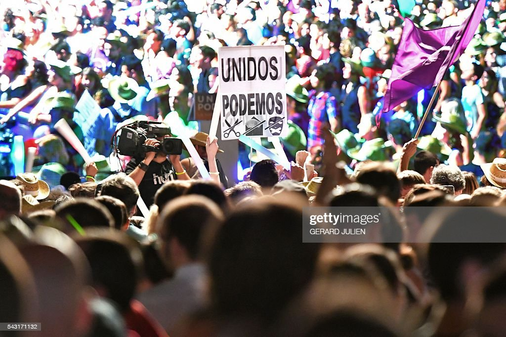 Supporters of left wing party Podemos hold a placard of far-left formation Unidos Podemos as they wait for official results at Reina Sofia square during Spain's general elections in Madrid on June 26, 2016. Spain's second elections in six months was due to conclude on June 26 in much the same way as they did in December, with the incumbent conservatives winning tailed by the Socialist party, partial results showed. / AFP / GERARD