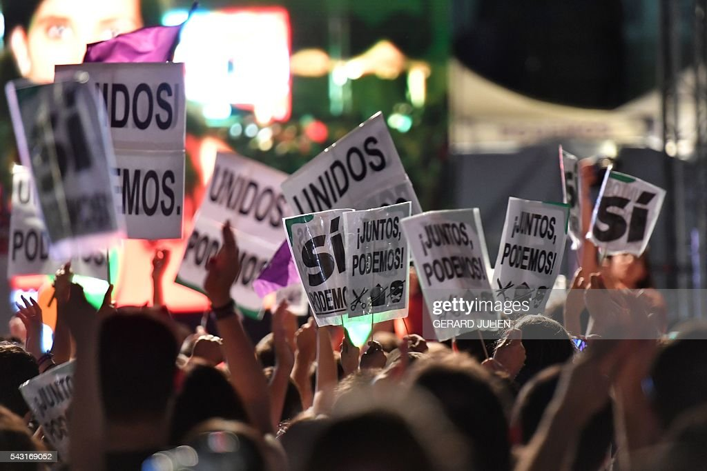 Supporters of left wing party Podemos hold placards as they wait for official results at Reina Sofia square during Spain's general elections in Madrid on June 26, 2016. Spain's second elections in six months was due to conclude on June 26 in much the same way as they did in December, with the incumbent conservatives winning tailed by the Socialist party, partial results showed. / AFP / GERARD