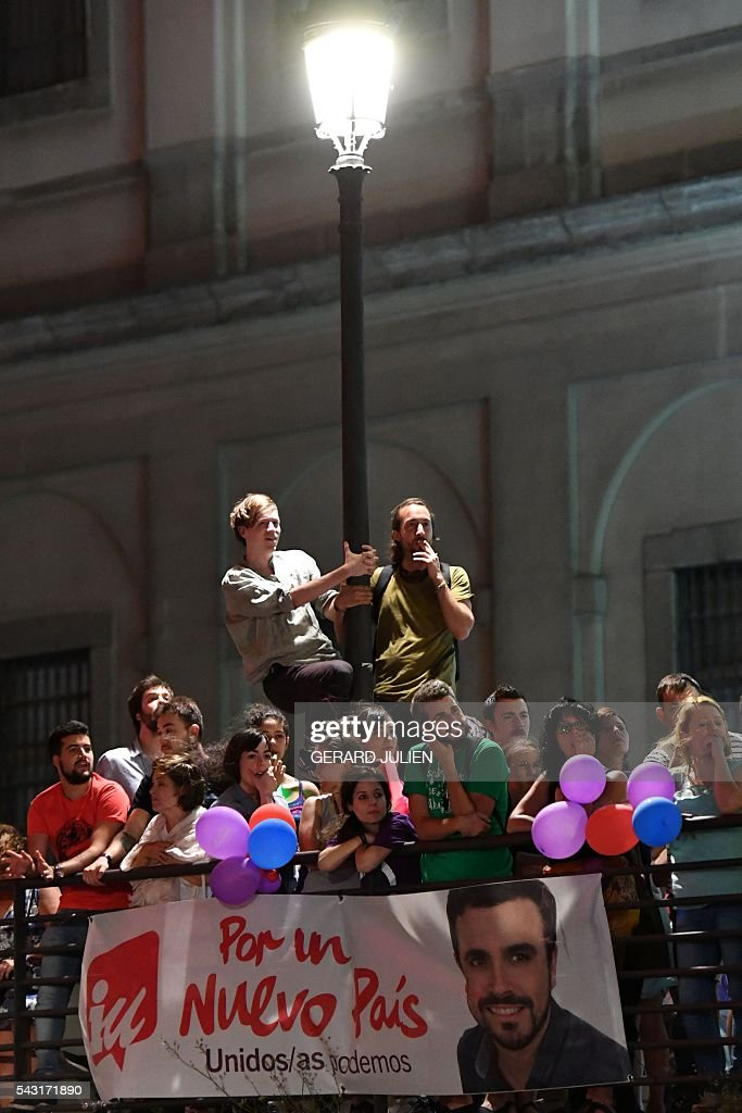 Supporters of left wing party Podemos wait for official results at Reina Sofia square during Spain's general elections in Madrid on June 26, 2016. Spain's second elections in six months was due to conclude on June 26 in much the same way as they did in December, with the incumbent conservatives winning tailed by the Socialist party, partial results showed. / AFP / GERARD