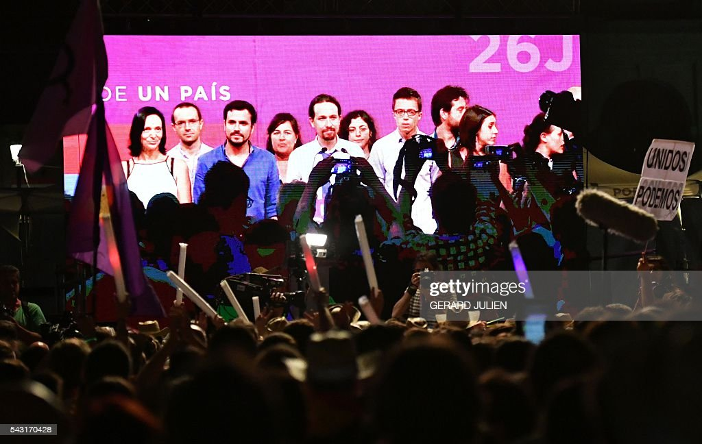 Supporters of left wing party Podemos watch leader of left-wing party IU Alberto Garzon (CL), leader of left wing party Podemos and party candidate, Pablo Iglesias (C) and policy secretary of left-wing party Podemos, Inigo Errejon (CR) on a giant screen as they wait for official results at Reina Sofia square during Spain's general elections in Madrid on June 26, 2016. Spain's second elections in six months was due to conclude on June 26 in much the same way as they did in December, with the incumbent conservatives winning tailed by the Socialist party, partial results showed. / AFP / GERARD