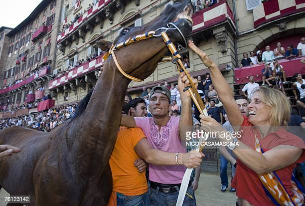 Supporters of Leocorno parish celebrate with her parish horse after the victory at the Palio horse race in the Piazza del Campo in Siena 16 Agoust...