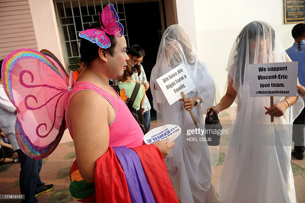 Supporters of lesbian, gay, bisexual, and transgender (LGBT) groups dressed in weddings gowns participate in a gay pride march at the University of the Philippines (UP) campus in Manila on June 27, 2013 as they celebrate Pride Month. UP celebrates Pride Month through its University Student Council and LGBT student organization with a message,Live Free! Youre safe in UP.