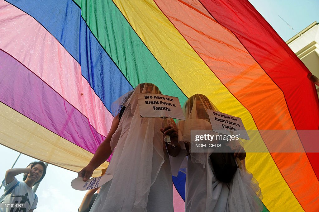 Supporters of lesbian, gay, bisexual, and transgender (LGBT) groups dressed in wedding gowns pose for a picture under a huge rainbow banner at the University of the Philippines (UP) campus in Manila on June 27, 2013 as they celebrate Pride Month. UP celebrates Pride Month through its University Student Council and LGBT student organization with a message,Live Free! Youre safe in UP.