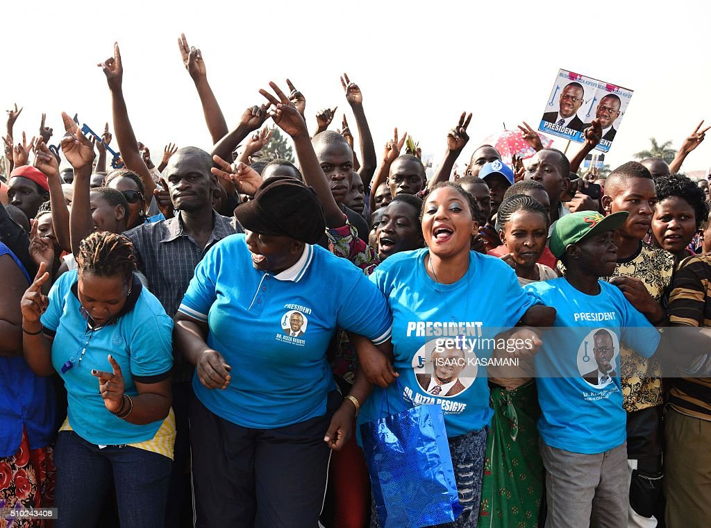 Supporters of main opposition presidential candidate Kizza Besigye from the Forum for Democratic Change (FDC) party, gather during a political rally in Wakiso District, in Kampala on February 14, 2016, two days before the Uganda's Presidential elections. Incumbent President Museveni is facing the hardest fight to keep his office as his main rival Kizza Besigye and his former Prime Minister Amama Mbabazi have gained country wide support. / AFP / ISAAC KASAMANI