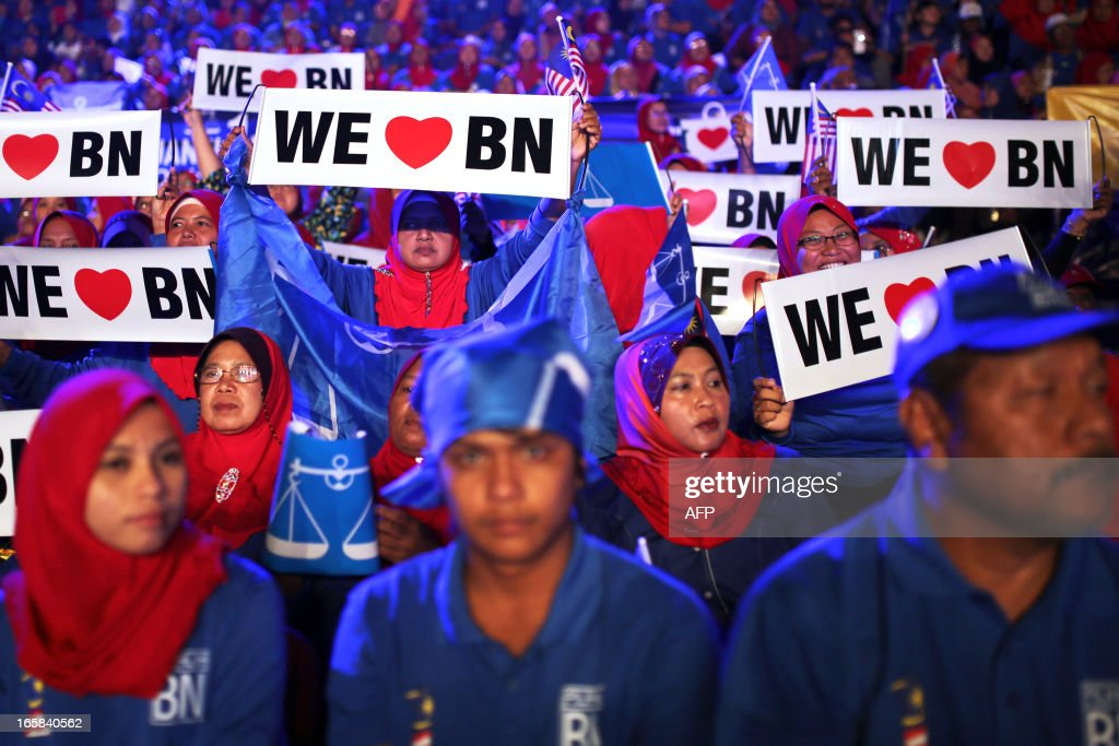 Supporters of Malaysia's ruling National Front coalition, or Barisan Nasional, wave banners during Malaysia's Prime Minister Najib Razak's launch of his election manifesto at the National Stadium in Bukit Jalil, a suburb of Kuala Lumpur, on April 6, 2013. Malaysia's premier Najib Razak unveiled a manifesto on April 6 pledging bigger cash handouts, millions of new jobs and lower taxes and crime, as he seeks his first mandate in looming national polls.