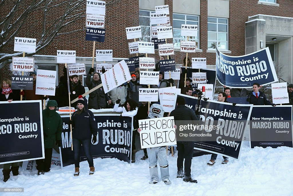 Supporters of many of the presidential candidates hold campaign signs and shout slogans outside the polling place at Webster School before the arrival of Republican presidential candidate Sen. Marco Rubio (R-FL) February 9, 2016 in Manchester, New Hampshire. With a good showing in the Iowa caucuses, Rubio has stepped into the crosshairs of fellow Republicans running for president and super PACs that want to slow his momentum with attacks on what they call his robotic and repetative messaging.