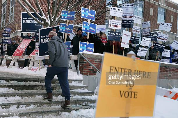 Supporters of many of the presidential candidates hold signs outside the polling place at the Webster School February 9 2016 in Manchester New...