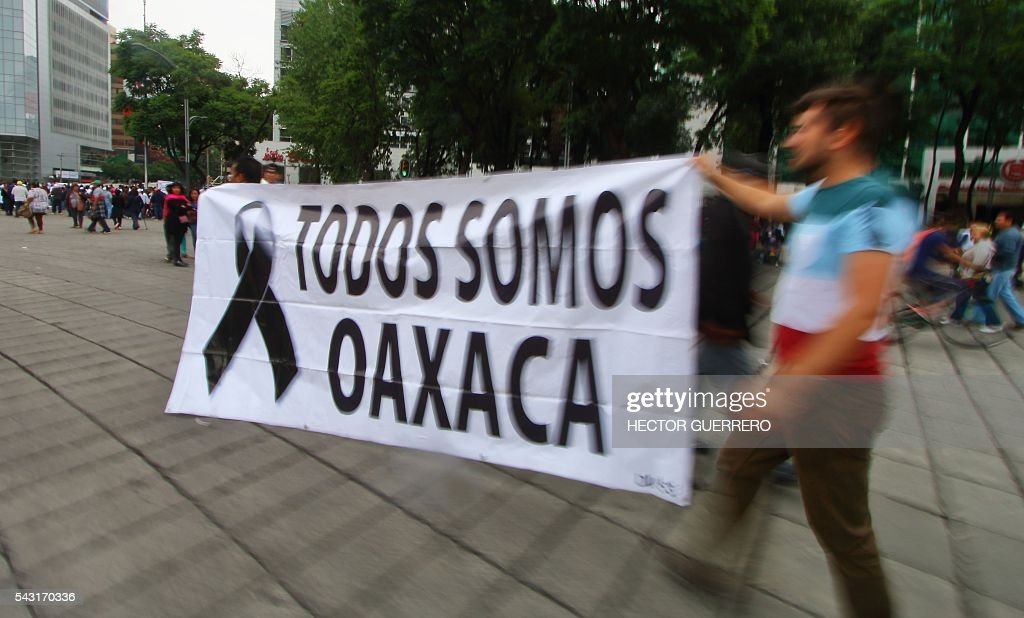 Supporters of Mexican leader of the National Regeneration Movement, Andres Manuel Lopez Obrador, hold a banner reading 'We are all Oaxaca' as they demonstrate in support of the National Coordination of Education Workers (CNTE) teachers' union, and against an education reform launhced by the government along Reforma Avenue in Mexico City on June 26, 2016. Eight people were killed after violent clashes following a teachers' protest last week in Oaxaca. / AFP / HECTOR