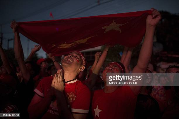 Supporters of Myanmar opposition leader Aung San Suu Kyi celebrate as they hear the official results of the elections on a giant screen outside the...