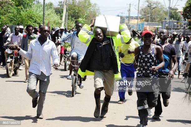 Supporters of National Super Alliance presidential candidate Odinga carry a computer mimicking IEBC servers during demonstrations calling upon the...
