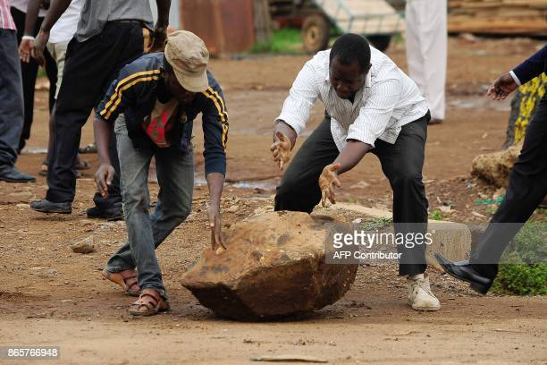 Supporters of National Super Alliance presidential candidate Odinga move a rock to barricade streets during demonstrations calling upon the boycott...