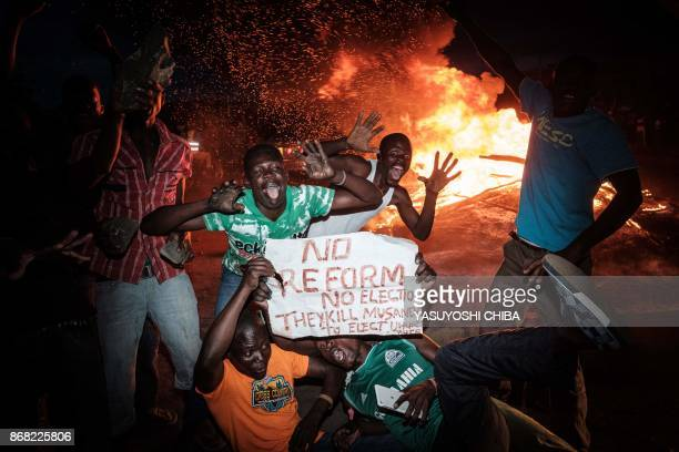Supporters of National Super Alliance presidential candidate Raila Odinga react after the result of reelections as the incumbent President declared...