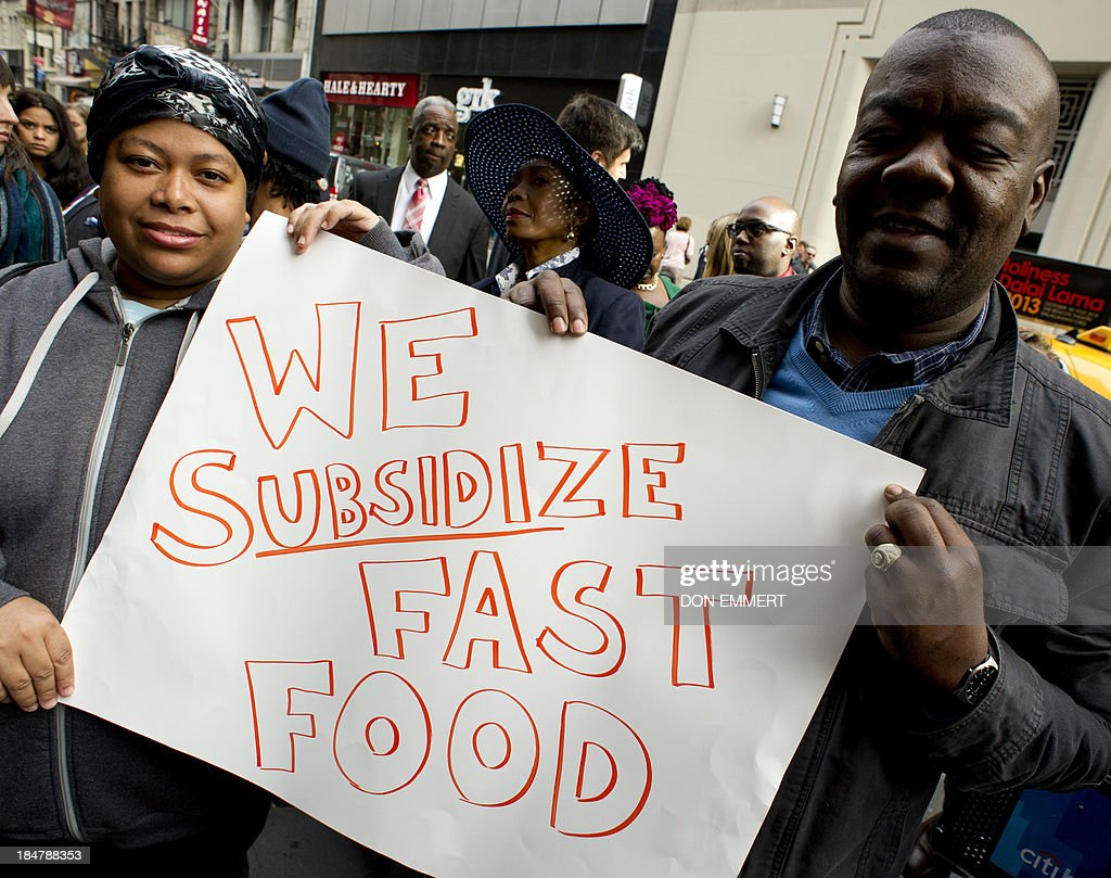 Supporters of New York City mayoral candidate Bill De Blasio outside a Burger King on October 16, 2013 in New York. De Blasio says low-wage fast food jobs are a cost to New York State taxpayers. He states that new research fromthe University of California, Berkeley, shows how low-wage, no-benefit fast food jobs force workers to rely on public assistance programs, leaving taxpayers to foot the bill. AFP PHOTO/Don Emmert