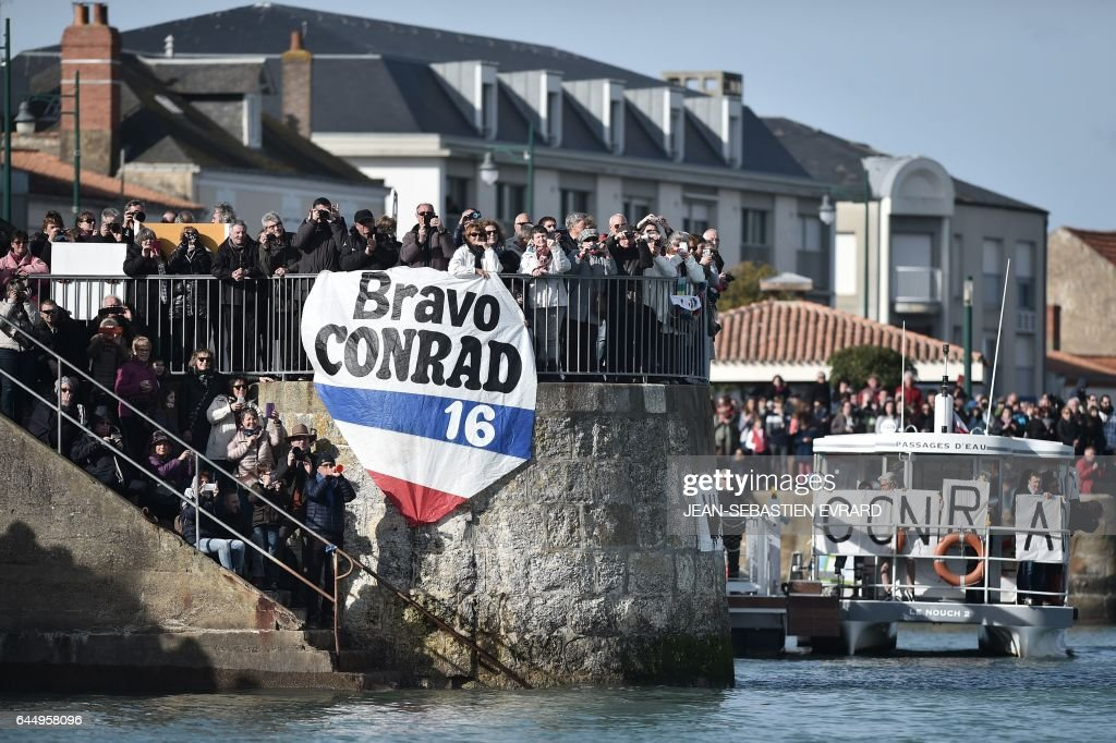 Supporters of New Zealand's skipper Conrad Colman hold a banner upon his arrival in Les Sables-d'Olonne, western France, at the end of the Vendee Globe around-the-world solo sailing race on February 24, 2017. Colman finished 16th. /