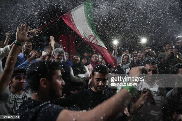 Supporters of newly reelected Iranian President Hassan Rouhani dance during a gathering to celebrate his victory at the Vanak square in downtown...