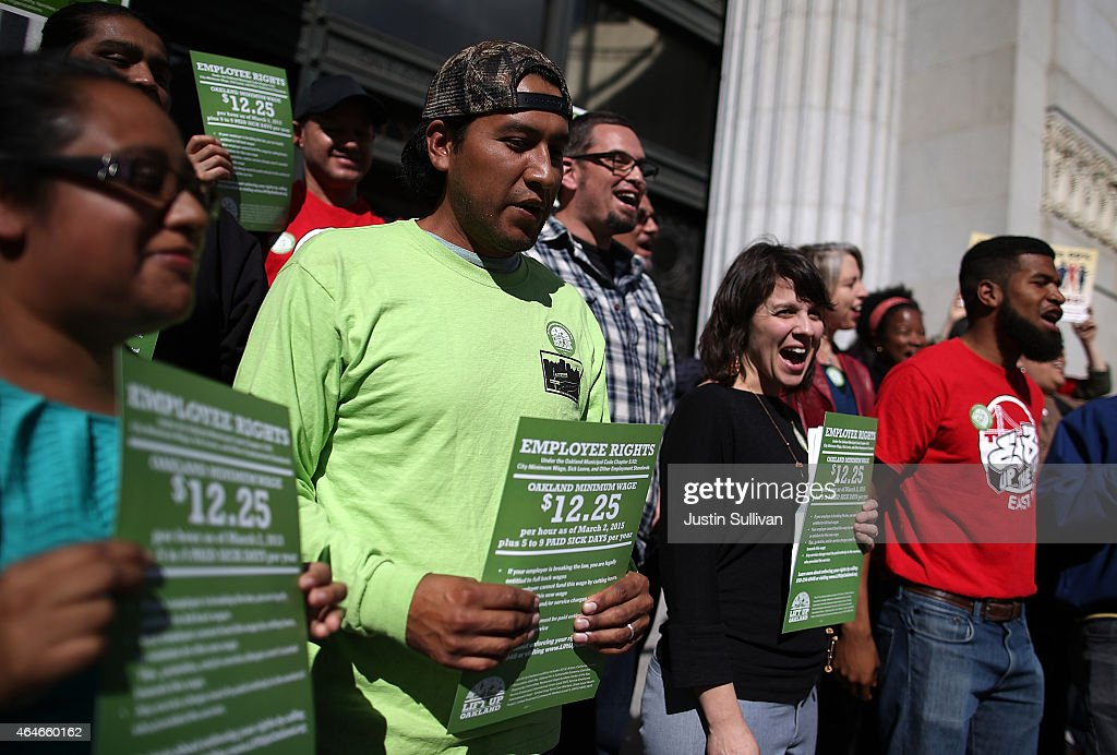 Supporters of Oakland's minimum wage increase hold signs during a celebration rally outside of Oakland City Hall on February 27 2015 in Oakland...