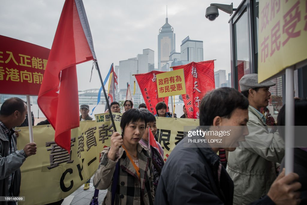 Supporters of of Hong Kong Chief Executive Leung Chun-ying march to the government headquarters to voice their discontent towards pro-democracy lawmakers and their supporters, during a protest in Hong Kong on January 9, 2013. Pro-democracy lawmakers were expected to table an impeachment motion on January 9 against chief executive Leung Chun-ying, demanding him to quit over a housing scandal. AFP PHOTO / Philippe Lopez