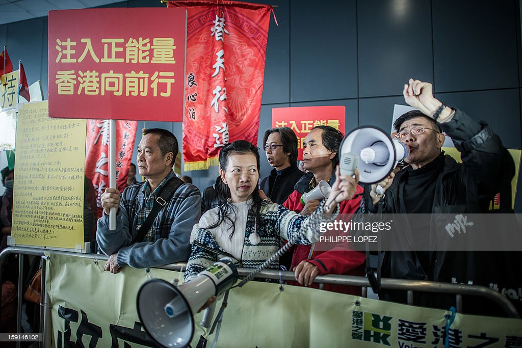 Supporters of of Hong Kong Chief Executive Leung Chun-ying shout slogans against pro-democracy lawmakers and their supporters during a protest in Hong Kong on January 9, 2013. Pro-democracy lawmakers were expected to table an impeachment motion on January 9 against chief executive Leung Chun-ying, demanding him to quit over a housing scandal. AFP PHOTO / Philippe Lopez