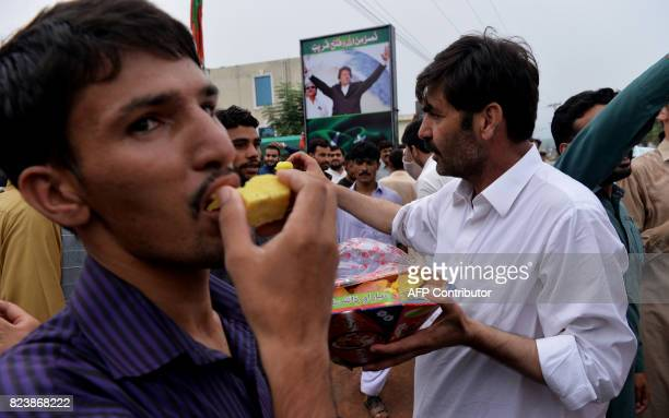 Supporters of opposition leader Imran Khan's Pakistan TehreekiInsaf eat sweets as they celebrate the Supreme Court decison against Pakistan's Prime...