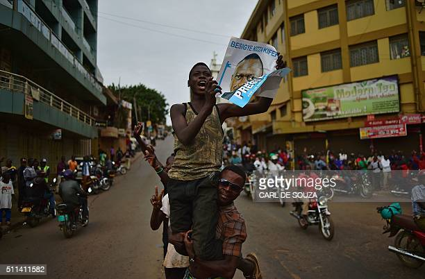 TOPSHOT Supporters of opposition leader Kizza Besigye cheer for him despite the announcement that President Yoweri Museveni has won the presidential...